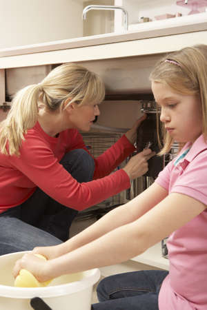 Daughter Helping Mother To Mop Up Leaking Sink Stock Photo - 9908744