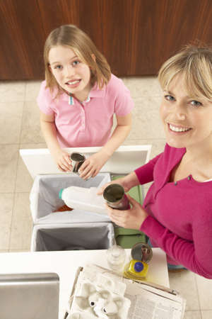 Mother And Daughter Recyling Waste At Home photo
