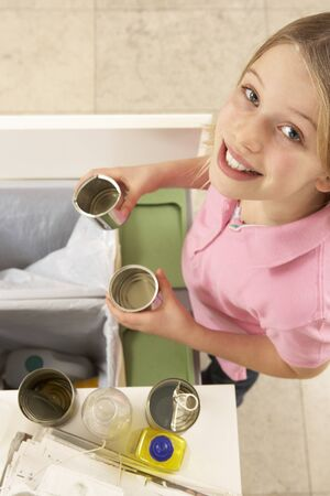 Young Girl Recyling Waste At Home photo