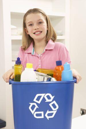 papelera de reciclaje: Chica sosteniendo Bin de reciclaje de residuos en el hogar Foto de archivo