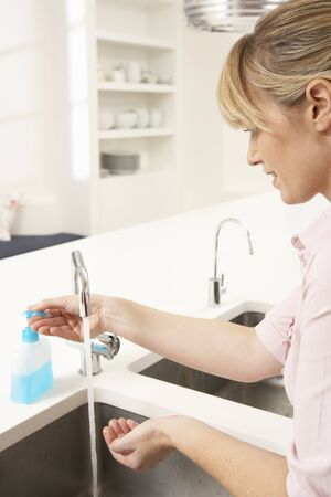 Woman Washing Hands At Kitchen Sink photo