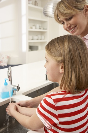 Mother And Daughter Washing Hands At Kitchen Sink photo