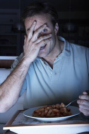 Frightened Man Enjoying Meal Whilst Watching TV Stock Photo - 9908870