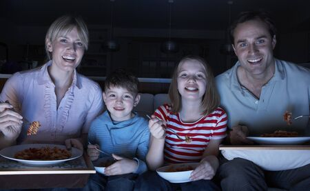 Family Enjoying Meal Whilst Watching TV Stock Photo - 9911268