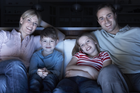 Family Watching TV On Sofa Together photo