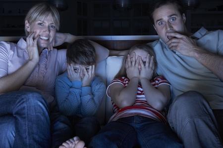 personas viendo tv: Familia viendo el programa de miedo en la televisi�n sentado en el sof� juntos