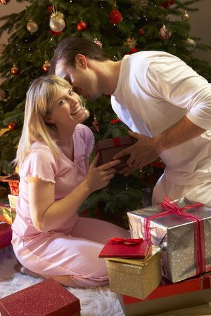 Couple Exchanging Presents In Front Of Tree photo