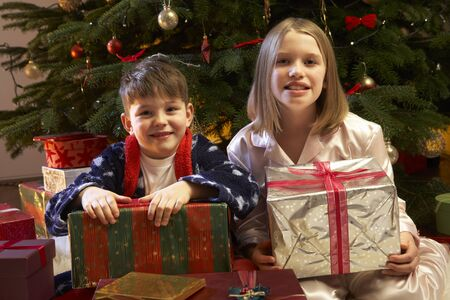 Children Opening Christmas Present In Front Of Tree photo