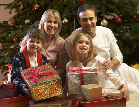 Family Opening Christmas Present In Front Of Tree photo