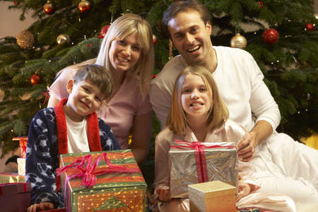 Family Opening Christmas Present In Front Of Tree Stock Photo - 9911178