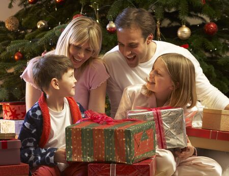 Family Opening Christmas Present In Front Of Tree Stock Photo - 9911274