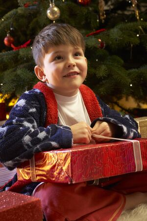 Young Boy Opening Christmas Present In Front Of Tree photo