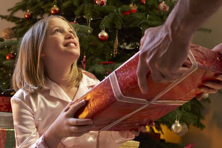 Young Girl Receiving Christmas Present In Front Of Tree photo