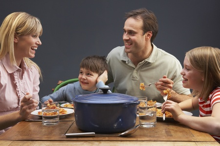 sitting at table: Family Enjoying Meal Together At Home Stock Photo