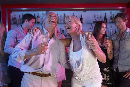 Senior Couple Having Fun In Busy Bar photo