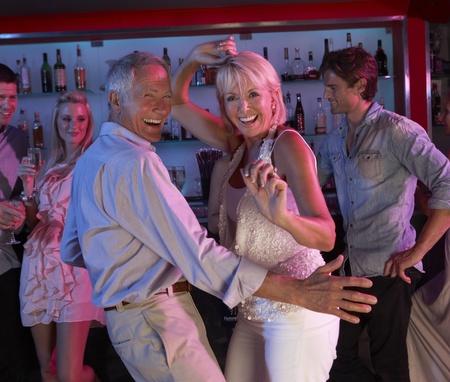donna che balla: Senior Couple Divertirsi In Bar Busy