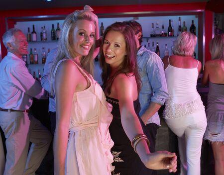 Two Young Women Having Fun In Busy Bar Stock Photo - 9908757