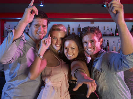 Group Of Young People Having Fun In Busy Bar photo