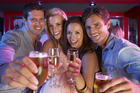 friends at bar: Group Of Young People Having Fun In Busy Bar Stock Photo