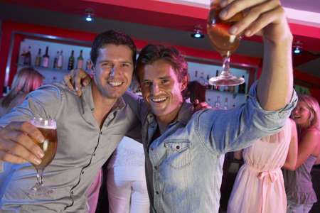 Two Young Men Having Fun In Busy Bar photo