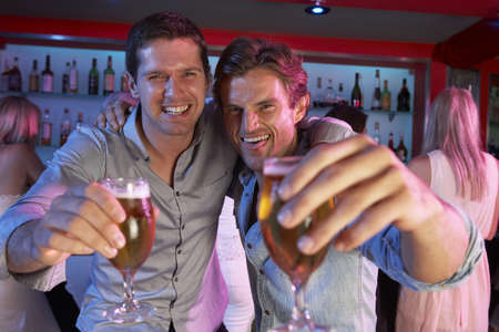 horizontal bar: Two Young Men Having Fun In Busy Bar