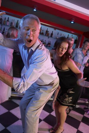 Senior Man Dancing With Younger Woman In Busy Bar photo