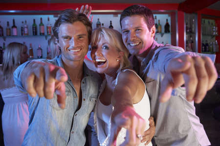 Senior Woman Having Fun In Busy Bar With Two Young Men photo
