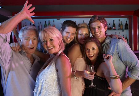 Group Of People Having Fun In Busy Bar photo