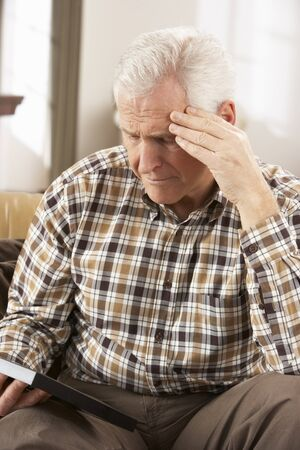 Sad Senior Man Looking At Photograph In Frame Stock Photo