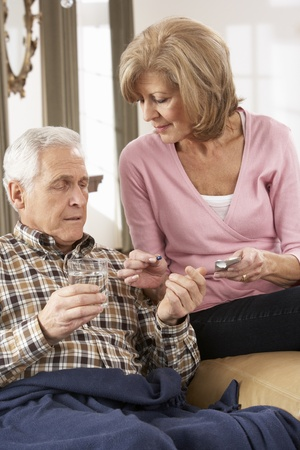 Senior Woman Caring For Sick Husband Stock Photo
