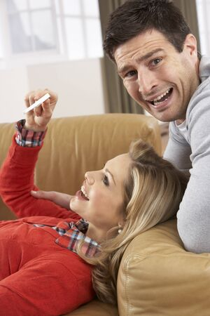 Couple Looking At Result Of Home Pregnancy Test Kit Stock Photo