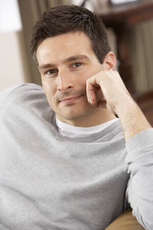 Young Man Relaxing In Chair At Home Stock Photo