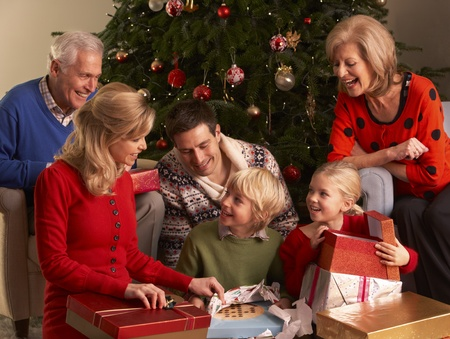 Three Generation Family Opening Christmas Gifts At Home Stock Photo