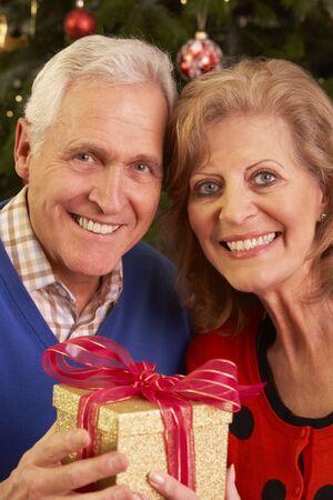 クリスマスプレゼントを交換するシニアカップル