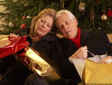 Tired Senior Couple Returning After Christmas Shopping Trip Stock Photo