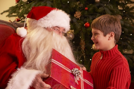 Santa Claus Giving Gift To Boy In Front Of Christmas Tree