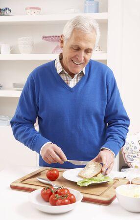 Senior Man Making Sandwich In Kitchen Stock Photo