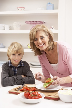 Grandmother And Grandson Making Sandwich In Kitchen