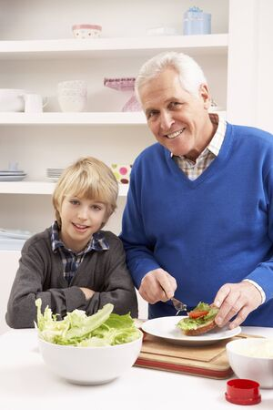 Grandfather And Grandson Making Sandwich In Kitchen