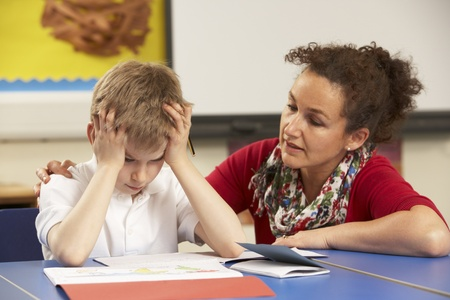 Stressed Schoolboy Studying In Classroom With Teacher photo