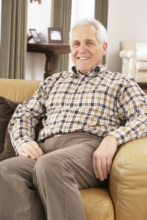 Senior Man Relaxing In Chair At Home Stock Photo