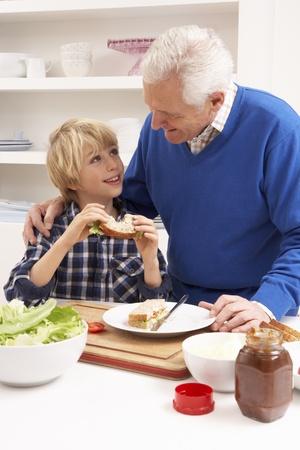 Grootvader en kleinzoon die Sandwich in keuken maken