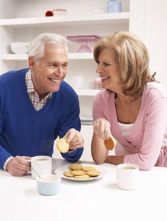 Ltere Paare, die heißes Getränk in der Küche genießen Standard-Bild - 85423631
