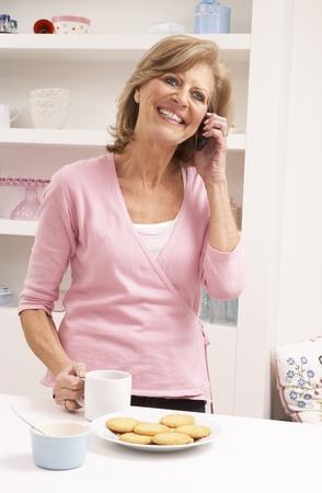 Senior Woman Enjoying Hot Drink Whilst On Phone