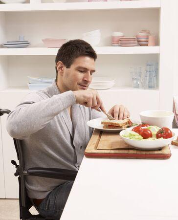 Disabled Man Making Sandwich In Kitchen