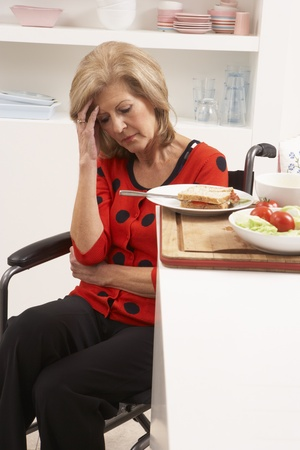 Distressed Disabled Senior Woman Making Sandwich In Kitchen