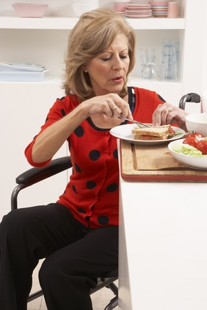 Disabled Senior Woman Making Sandwich In Kitchen Stock Photo