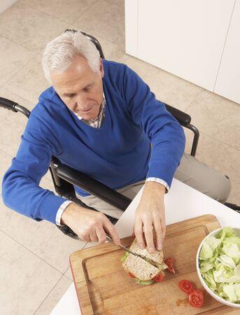 Disabled Senior Man Making Sandwich In Kitchen Stock Photo