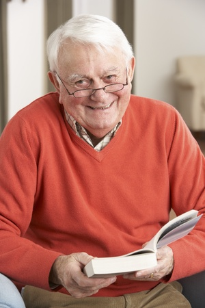 Senior Man Relaxing In Chair At Home Reading Book Stock Photo - 9911148