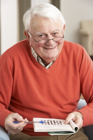 Senior Man Relaxing In Chair At Home Completing Crossword Stock Photo - 9911306